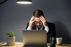 Portrait of tired anxious male worker with headache. Stressed man in glasses holding head in hands, looking at laptop and thinking about deadline. Overwork, negative thoughts, deadline concept.
