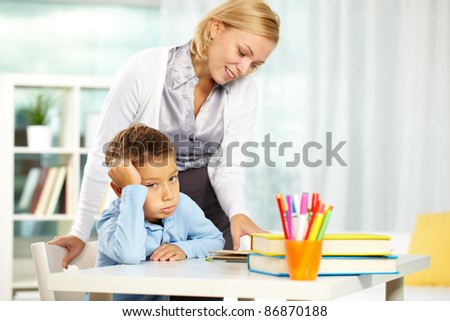 Portrait of tired boy looking at camera while tutor explaining something near by