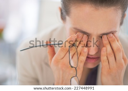 Portrait of tired business woman with eyeglasses in office Foto stock ©