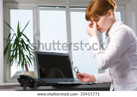 Portrait of tired businesswoman with his eyeglasses off keeping his hand after hard working day