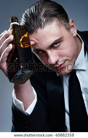 Portrait of tired drunk man with whiskey bottle