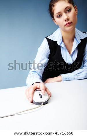 Portrait of tired female keeping her hand on computer mouse