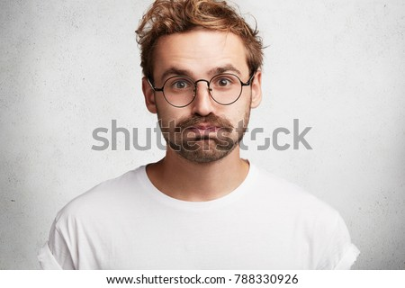 Portrait of tired stylish bearded intelligent male student gives deep sigh, presses lips, feels relief after passed exam, isolated over white background. Handsome young unshaven man poses indoor. #788330926