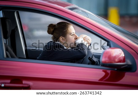 Portrait of tired woman driving car and looking through window