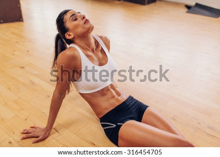 Portrait of tired woman having rest after workout. Tired and exhausted female athlete sitting on floor at gym.