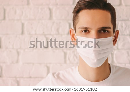 Portrait of tired young man in white medical mask on face for personal protection during coronavirus COVID-19 pandemic. Exhausted confident doctor wearing protective face mask. Prevention of nCov-19