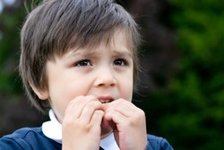 Portrait of toddler boy biting his finger nails while looking at some thing at the park, Childhood and family concept, emotional child portrait