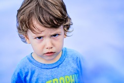 Portrait of toddler boy with angry upset face expression