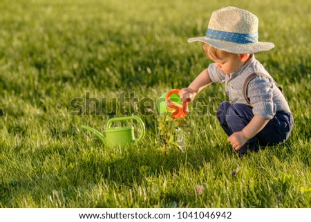7873986fb25 Portrait of toddler child outdoors. Rural scene with one year old baby boy  wearing straw
