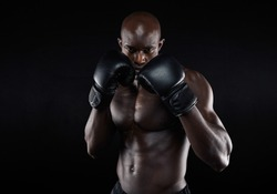 Portrait of tough male boxer posing in boxing stance against black background. Professional fighter ready for boxing match.