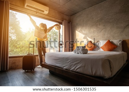 Portrait of tourist woman raised her hands and standing nearly window, looking to beautiful view with her luggage in hotel bedroom after check-in. Conceptual of travel and vacation.