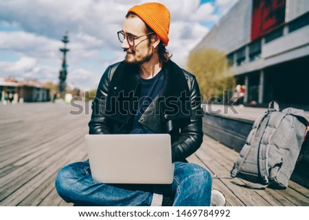 Portrait of trendy dressed hipster guy sitting with laptop computer for e learning outdoors satisfied with 4G internet connection, prosperous male freelancer enjoying sunny day on publicity area
