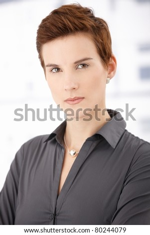 Portrait of trendy ginger woman with short hair style, looking at camera.?