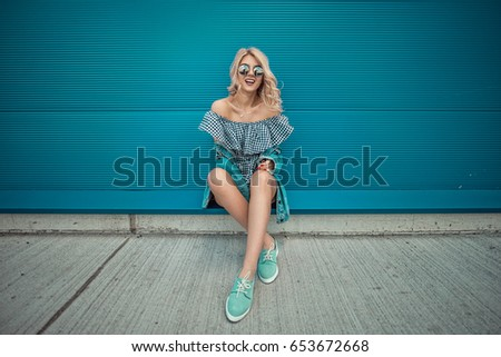 Portrait of Trendy Hipster Girl sitting at the blue turquoise wall Background. Urban Fashion Concept. Copy Space.