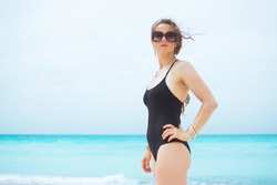 Portrait of trendy middle age woman with long curly hair in elegant black bathing suit on a white beach looking into the distance.