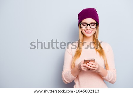 Portrait of trendy style stylish  smart clever excited cute lovely cute sweet teenage girl with long blonde hair using smartphone for sending and receiving messages isolated gray background copy-space