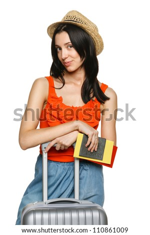 Portrait of trendy young female in wicker hat standing with suitcase and holding passport with tickets, over white background