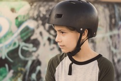 Portrait of trendy young skater at the skatepark wearing helmet, looking away. Smiling teenager enjoying sunny day outdoors in the city with skateboard. Youth, health, safety, sport, positive concept