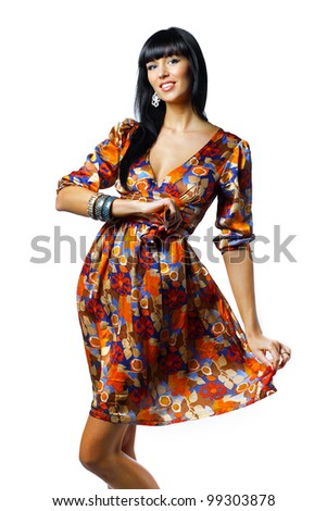 Portrait of trendy young woman in funky orange dress smiling against white background