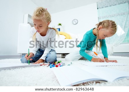 Portrait of twin girls drawing at home - stock photo