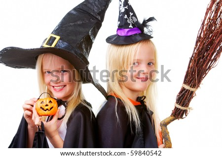 Portrait of twin girls in black hats and black clothing - stock photo