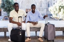 Portrait of two african american travelers sitting with luggage on bench on city street in summer