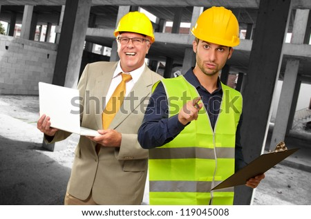 Portrait Of Two Architect Engineers Holding Laptop And Writing Pad, Indoors