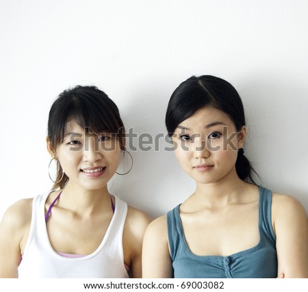 Portrait of two Asian girls leaning on wall