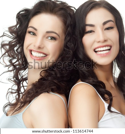 portrait of two attractive  caucasian  and asian smiling women brunette isolated on white studio shot