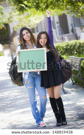 Portrait of Two Attractive Excited Mixed Race Female Students Holding Blank Chalkboard and Carrying Backpacks on School Campus.