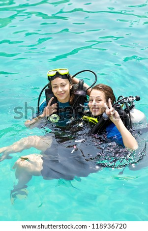 Portrait of two attractive friends going scuba diving