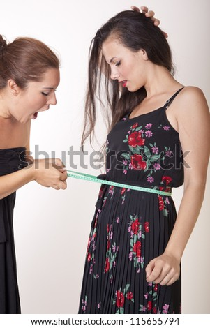Portrait of two attractive women with measuring tape.