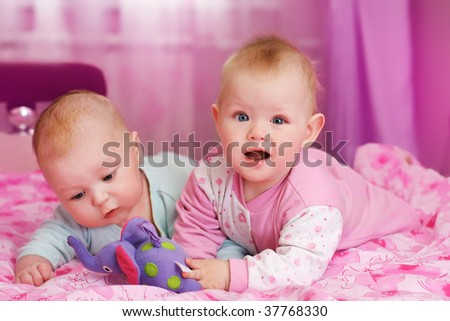 stock photo : portrait of two babies in pink room