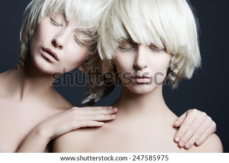 Stock Photo Portrait of two beautiful girls twins with closed eyes in studio