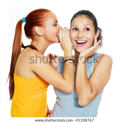 portrait of two beautiful gossiping girls against white background