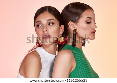 Portrait of two beautiful sexy woman perfect face cosmetic skin care beauty salon hairdo hair style model blush mascara lipstick collection accessory jewelry earrings cream young pure lotion friends.