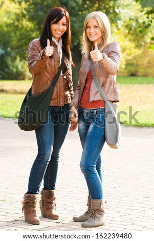 Portrait of two beautiful students showing ok sign,Thumbs up for education - stock photo