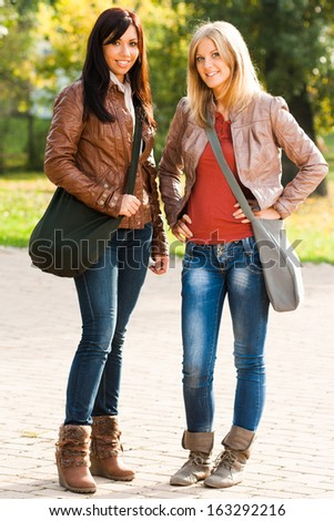 Portrait of two beautiful students standing in the park,Students - stock photo