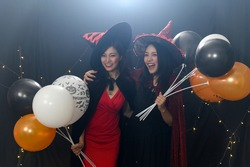 Portrait of two beautiful young woman in witch halloween costumes at party over dark magic background - Halloween party concept