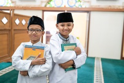 portrait of two boys holding holy quran standing and smile in the mosque