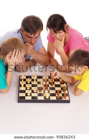 portrait of two boys playing chess with parents