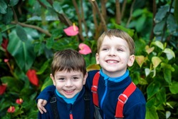 Portrait of two boys, siblings, brothers and best friends smiling. Friends hugging. Happy kids wearing warm closes in orangery park