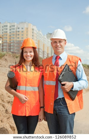 Portrait of two builders standing at building site