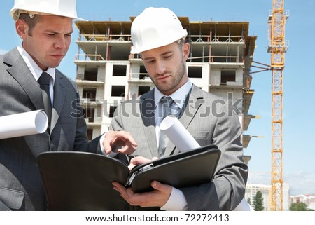Portrait of two builders standing at building site and discussing new project held by one of them #72272413