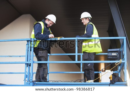 Portrait of two builders standing on platform at building site. The foreman is signing papers.