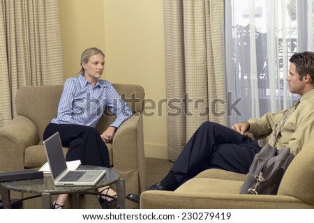 Portrait of two business people having a meeting in a living room