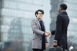 Portrait of two business people, Middle-eastern and African, meeting in snowy city street, smiling, shaking hands and greeting each other