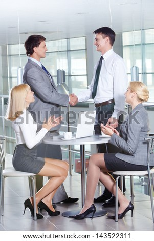 Portrait of two businessmen handshaking while females applauding