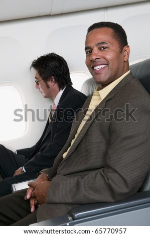 Portrait of two businessmen on airplane