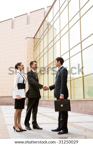 Portrait of two businessmen shaking hands after signing contract with pretty employee standing near by